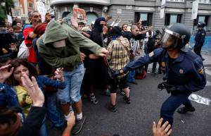 A policeman clubs a protester after police charged demonstrators outside the the Spanish parliament in Madrid